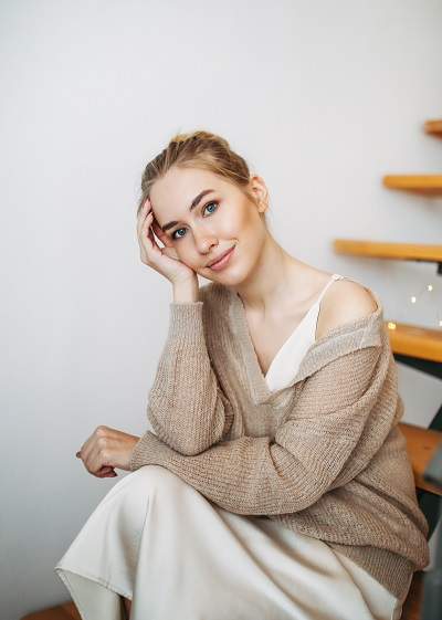 Young beautiful Russian girl in an evening beige silk dress and cozy cardigan sitting on stairs at home