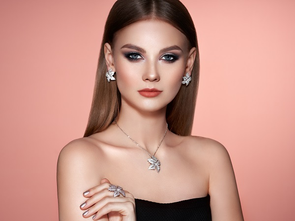 Brunette Russian woman with long shiny smooth hair wearing silver earrings and necklace