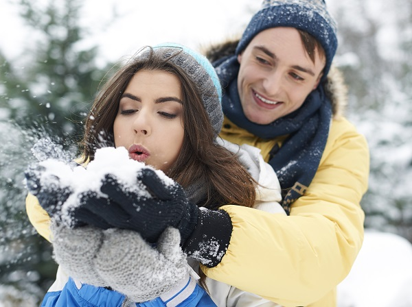 Beautiful charming Russian lady walking with her boyfriend playing with snow while posing