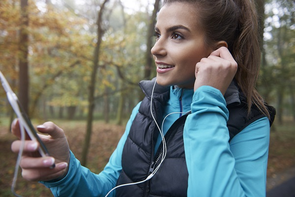 Young sexy Russian girl going out on jogging with earphones and a cellphone in the early morning